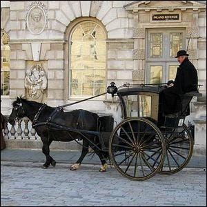 A traditional horse-drawn black cab in London