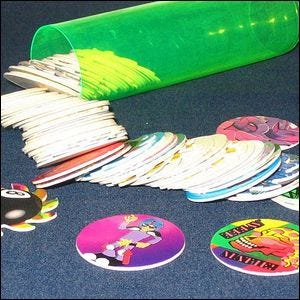A tube of pogs, spread out across a tabletop