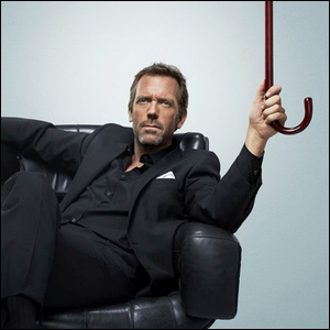 Hugh Laurie sitting in a leather chair holding the cane used in the role for the TV show House