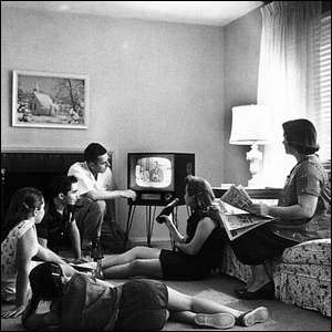 Midcentury family watching television on a black and white television set