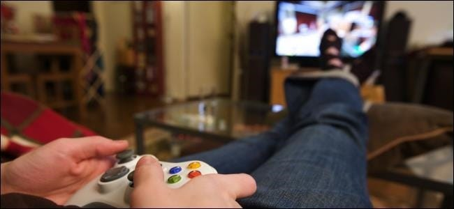 An image of a person with their feet up playing a video game.