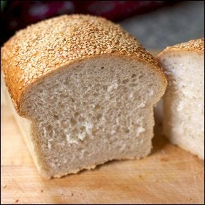 A loaf of wheat bread with a sesame seed crust