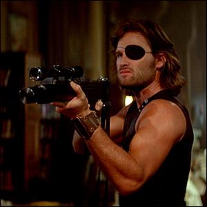 Kurt Russell holding a gun and wearing an eye patch as Snake