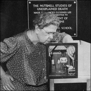 Photo of Frances Glessner Lee showing off one of her miniature dollhouse dioramas.