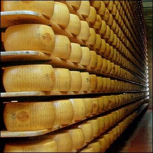 A cheese aging storeroom with hundreds of wheels of cheese stacked up on shelves