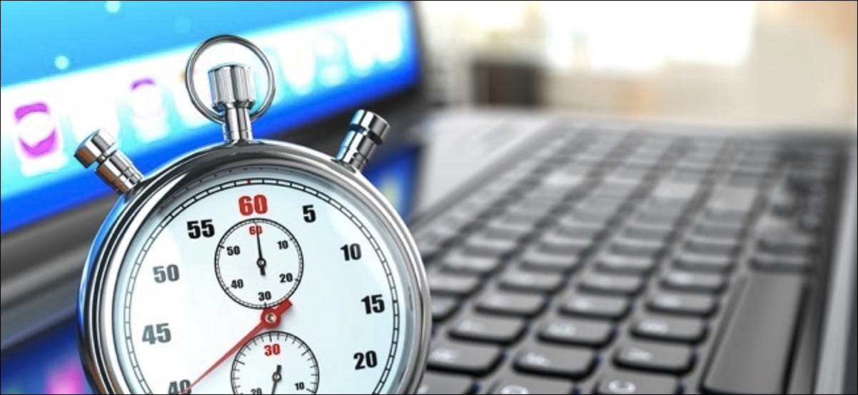 Stopwatch on laptop keyboard. Deadline concept.