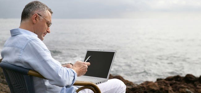 Portrait of a man sitting with a laptop computer face to the sea