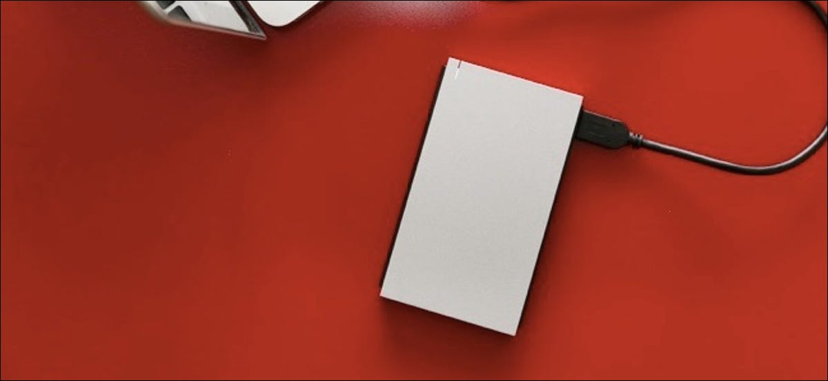 Top view of external hard drive connected to laptop on the red table