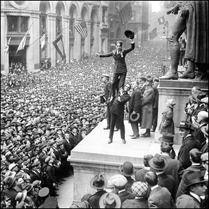 Men crowding Wall Street in the early 20th century.