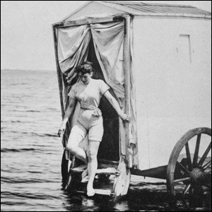 A woman stepping out of a bathing machine into the ocean.