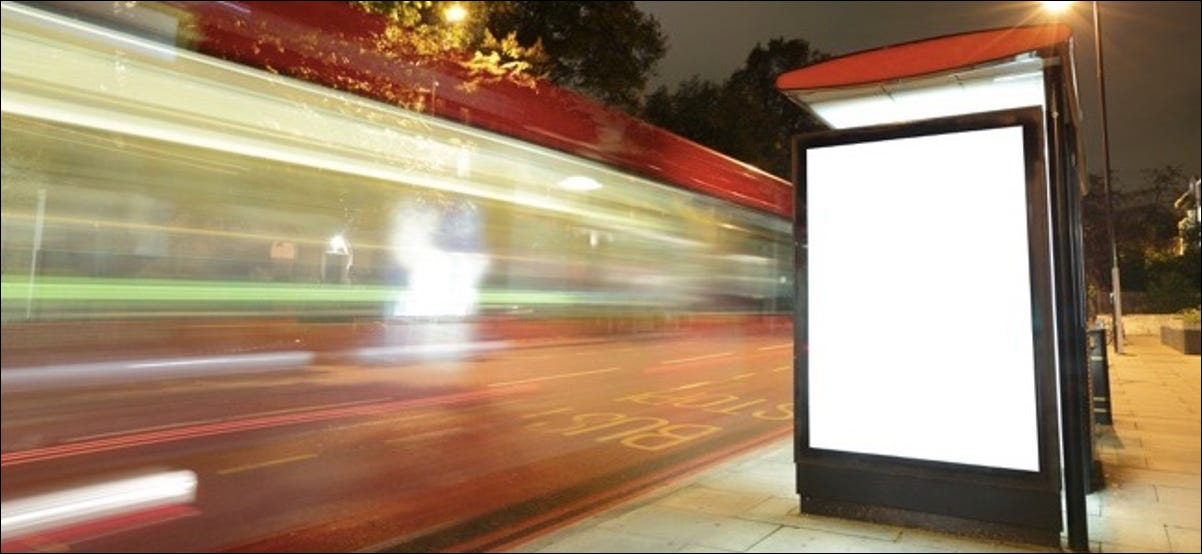 Blank billboard in bus stop at night with the lights of the cars passing by great copy space for your design shot in London United Kingdom uk