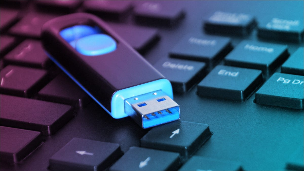 flash drive laying on top of a laptop computer's keyboard