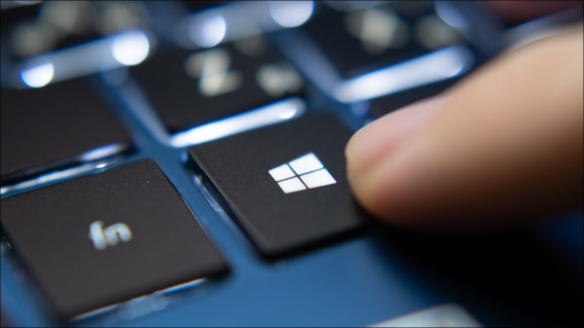 A finger pressing a backlit Windows key on a PC keyboard.