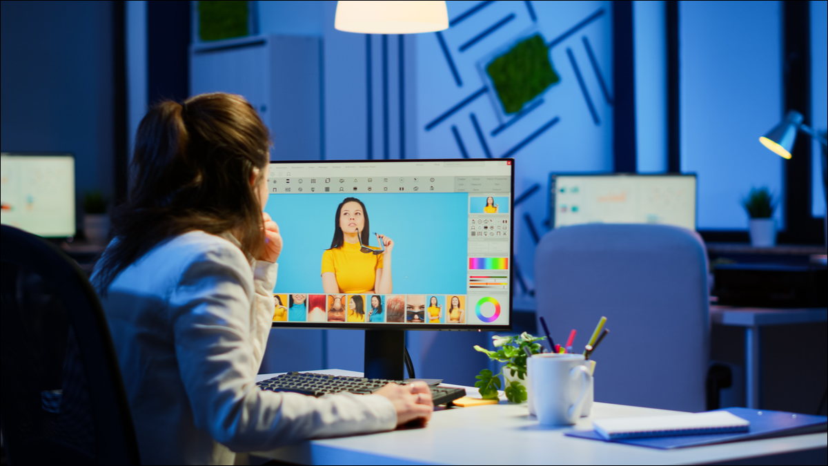 A woman viewing and editing photos on a Windows desktop PC.