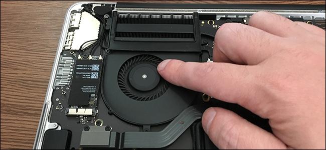 A finger touching the cooling fan inside a MacBook Pro.