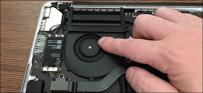 A finger touching the cooling fan inside a MacBook Pro.