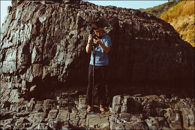 Man adjusting camera on monopod in front of cliff face