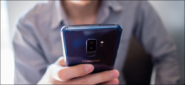 man holding blue Android phone