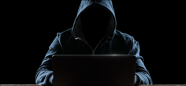 Hooded hacker at laptop computer
