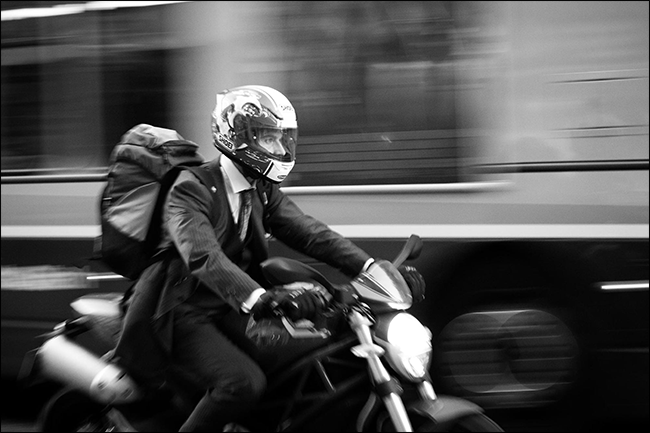man in suit riding motorcycle with blurred bus moving behind him