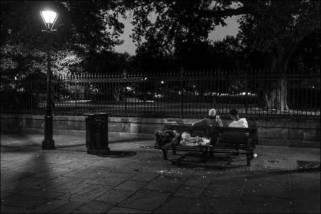 two men sitting on park bench at night; one man sleeping on seat behind them