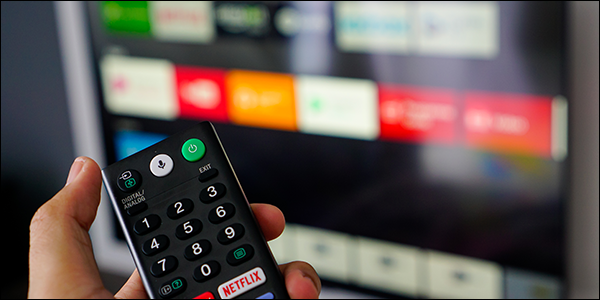 Hand holding the remote for a smart TV