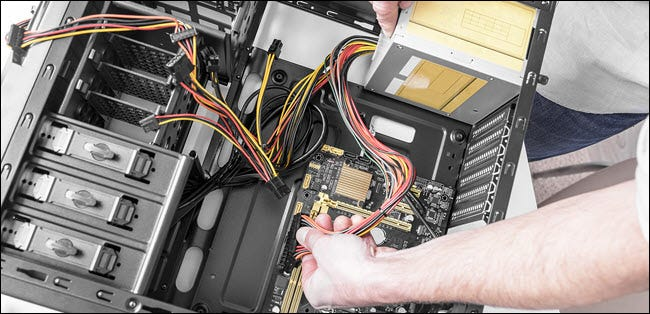 technician installing power supply in a PC