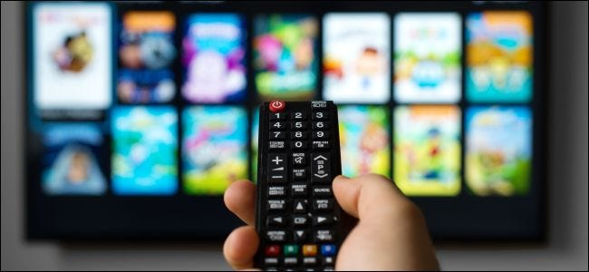 male hand holding remote control pointed at television