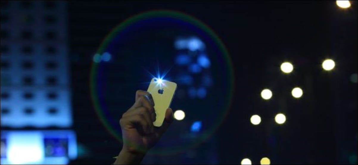 iPhone raised in the air during night time protest