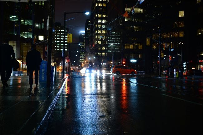 People walking Toronto streets at night in the rain