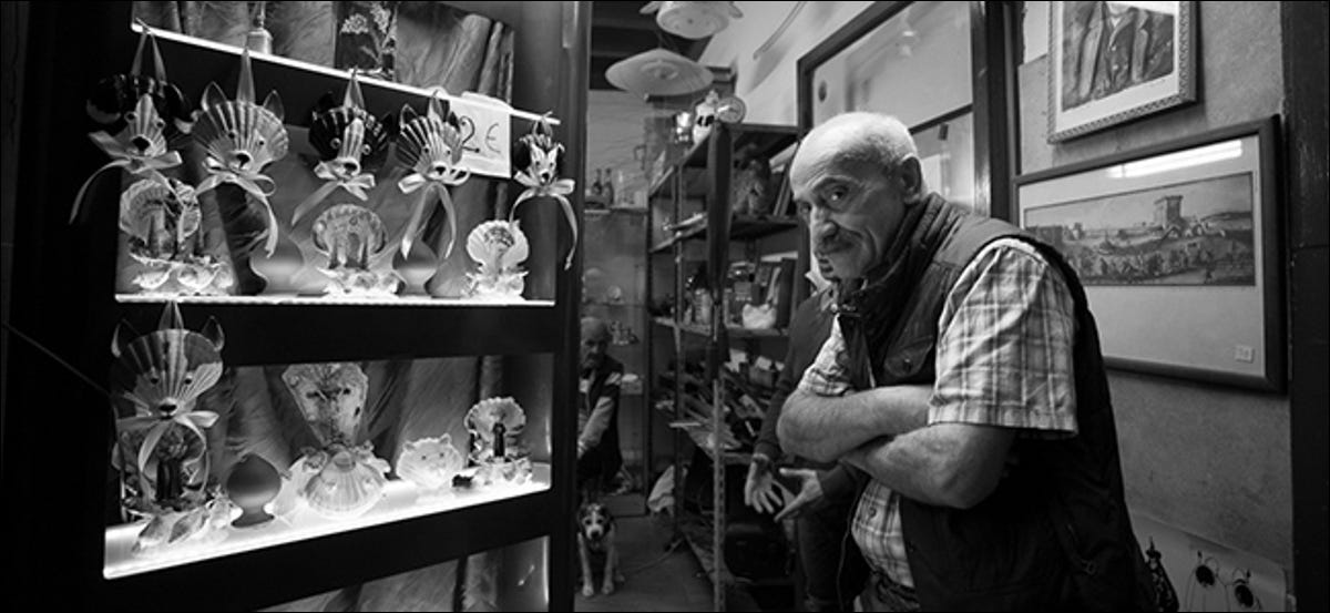 Older man with folded arms in curio shop