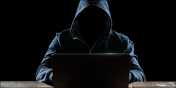 mysterious nerdy man in a hoodie hacking into a laptop