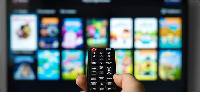 Man pointing a TV remote at a smart TV