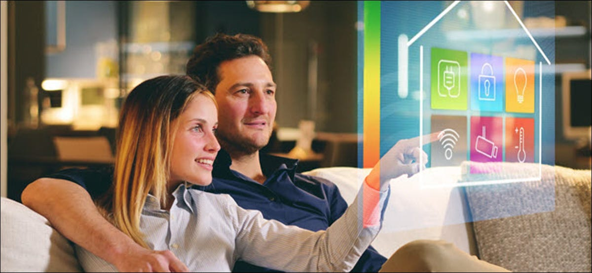 A couple sitting on the sofa controls all the functions of the house such as wi-fi, heating, lighting, television through holography. Concept of, home automation, automations, future, technology