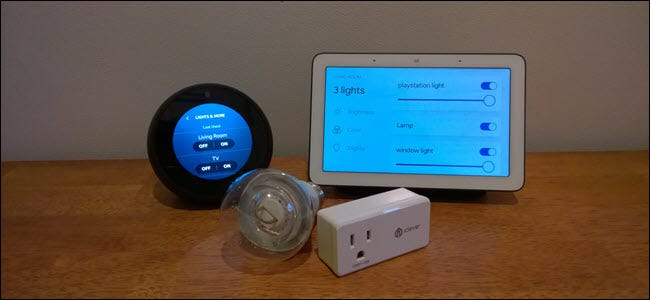 A Google home hub and Echo spot in front of a smart outlet and light bulb