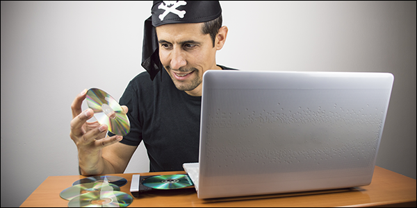 man dressed as a pirate smiling as he places CD's inside of his laptop