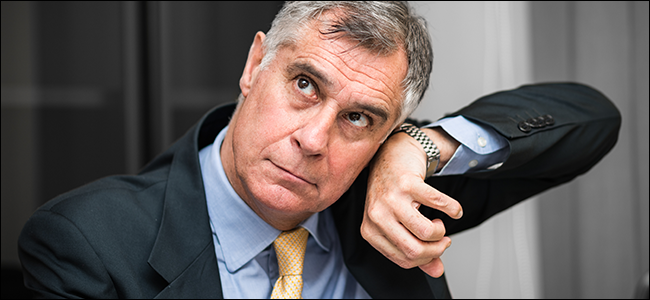 A man pressing his watch to his ear