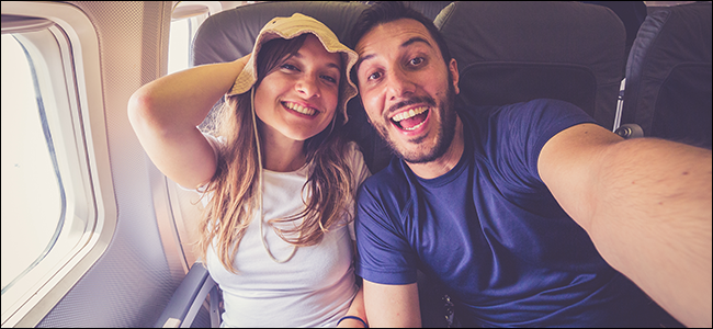 A young couple taking a selfie on an airplane
