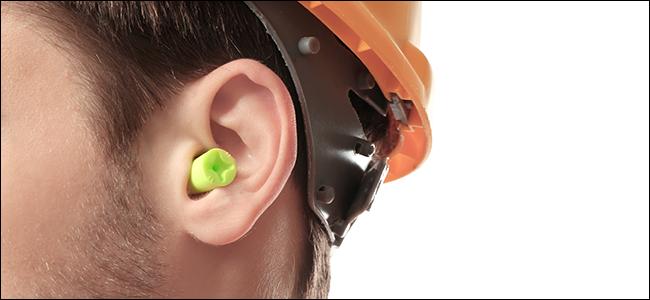 A man in a hard hat wearing earplugs
