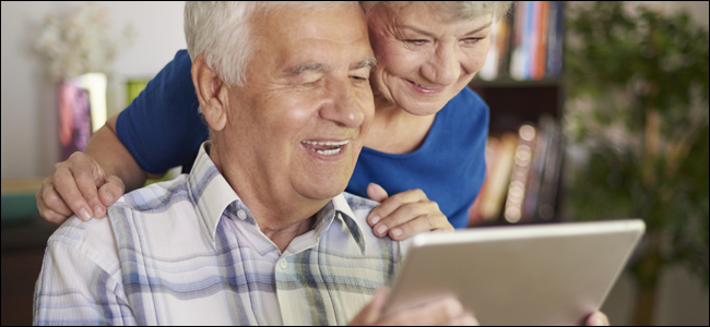 Elderly couple smiling while playing with a tablet