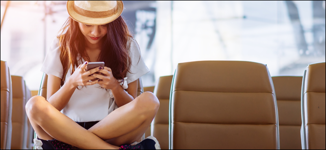 Young woman using her phone at an airport