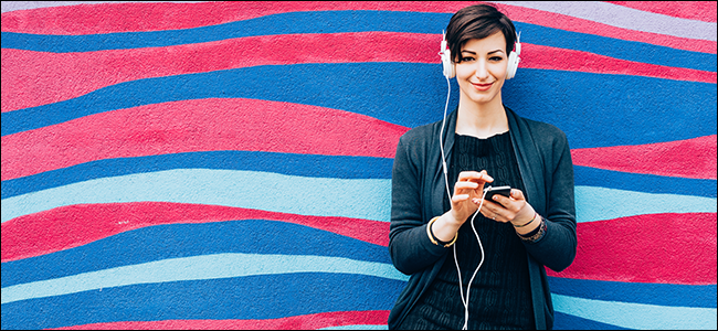A woman smiles while listening to music through headphones