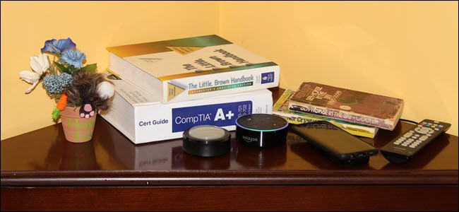 An Echo and Echo button on a nightstand near cellphone, books, and a plant.