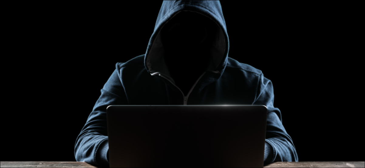 Shadowed person in a hood typing on a laptop.