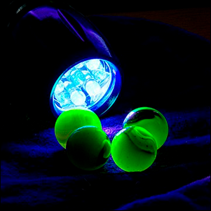 Uranium glass marbles glowing in front of a UV flashlight
