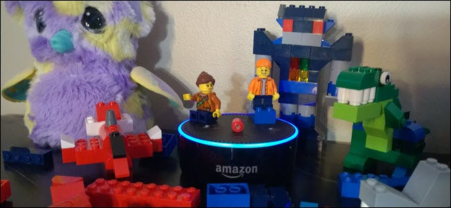 An Echo Dot surrounded by Lego blocks, minifigs, and a Hatchimal