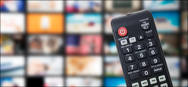 A TV remote with a backdrop of streaming services and TV channels.