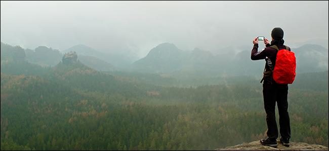 A man taking a photo of a dramatic, foggy mountain range.
