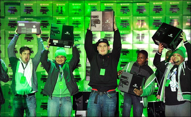 Several Microsoft contumers holding up new Xbox One consoles on launch day
