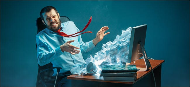 Young stressed handsome businessman working at desk in modern office shouting at laptop screen and being angry about e-mail spam. Collage with a mountain of crumpled paper.